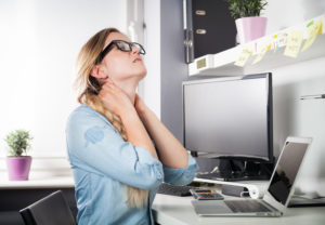 Woman sitting at desk in office suffering from neck pain. For relief from your desk pain seek our Schererville Back Pain Relief.