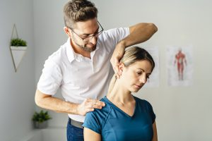 A woman getting help from a chiropractor at his office, representing how one can benefit from calling a Crown Point chiropractor.