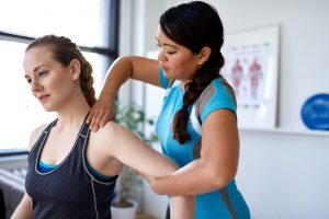 A female chiropractor massaging an an athlete. Representing how one can benefit from calling a Crown Point chiropractor.