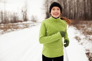 A woman running on snow covered path, stay active if any strain on muscles contact our good St. John Chiropractor Office.