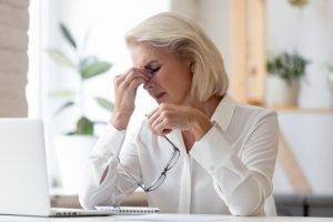 Female with migraine pain while at work, Chiropractic Treatments Crown Point can help relieve your chronic pain.