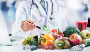 A nutritionist pointing at fruit and vegetables, visit our nutritionist today