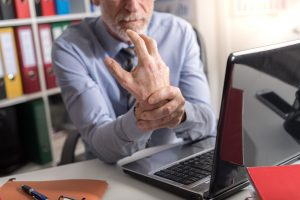 Man sitting at desk holding wrist in pain, arrange an appointment with NW Indiana Chiropractic Office for pain treatment.