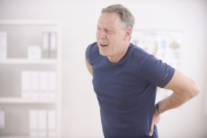 Man expressing back pain, make an appointment with a good Chiropractor Cedar Lake for massage therapy.