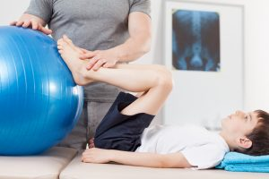 Small boy doing exercises suggested by Schererville Chiropractor.