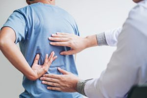 Doctor feeling patients back for pain, Crown Point Chiropractor