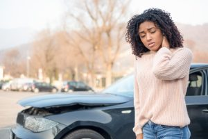 Woman standing in front of car accident wearing a pink shirt and rubbing her neck