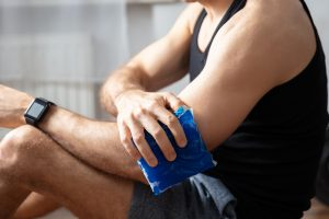 Man holding icepack onto bicep, wqearing a watch- Crown Point Chiropractors