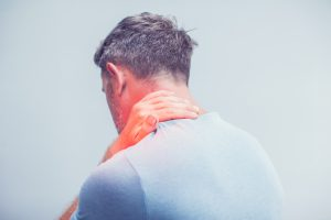 Man holding his neck from muscle strain, visit Neck Pain Treatment Crown Point.